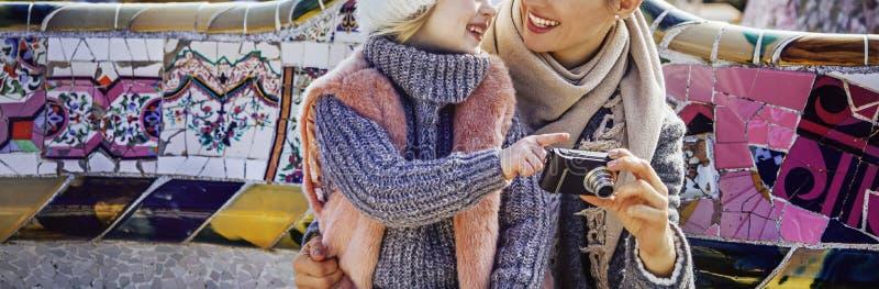 Szczęśliwe matki i dziecka viewing fotografie na kamerze przy Guell parkiem obrazy stock