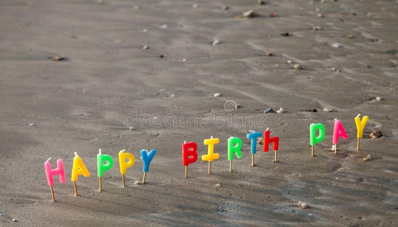 Szczęśliwe narodziny dnia listu świeczki w piasku fotografia stock