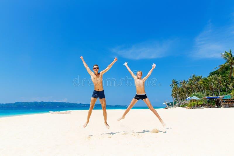 Szczęśliwe nastoletnie chłopiec ma zabawę na tropikalnej plaży Lata vacatio fotografia stock