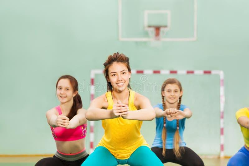 Szczęśliwe nastoletnie dziewczyny robi gimnastykom w gym obrazy royalty free