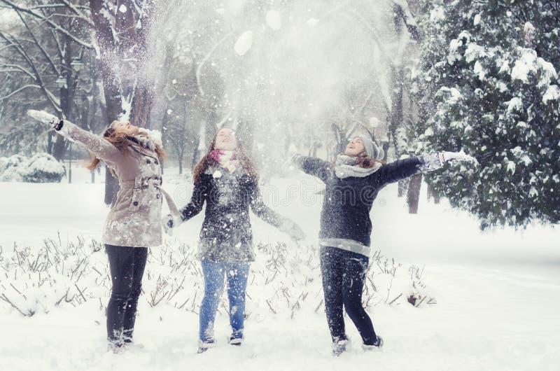 Szczęśliwe nastoletnie dziewczyny rzuca śnieg w powietrzu zdjęcie stock