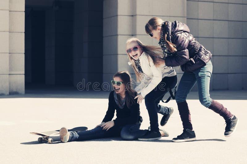 Szczęśliwe nastoletnie dziewczyny z deskorolka na miasto ulicie obraz stock