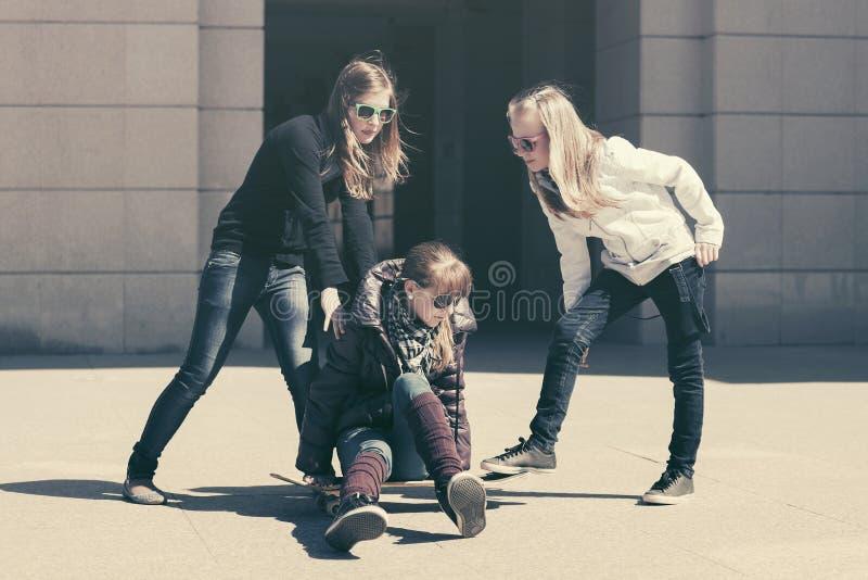 Szczęśliwe nastoletnie dziewczyny z deskorolka w miasto ulicie zdjęcie royalty free
