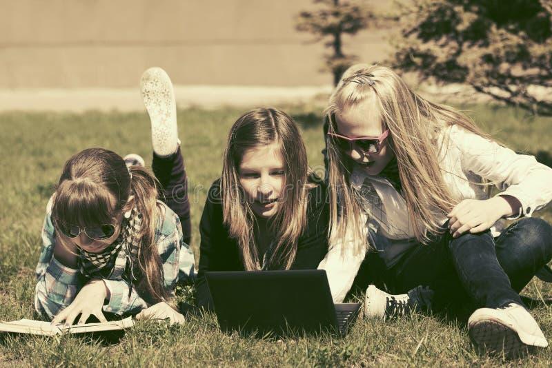 Szczęśliwe nastoletnie szkolne dziewczyny kłama na trawie w kampusie obraz stock