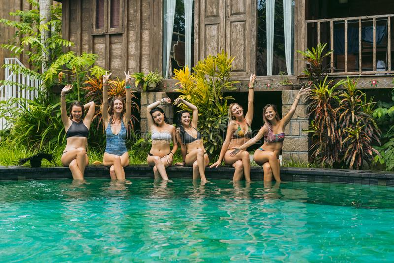 szczęśliwe piękne dziewczyny w swimwear obsiadaniu przy basenem i ono uśmiecha się zdjęcie royalty free