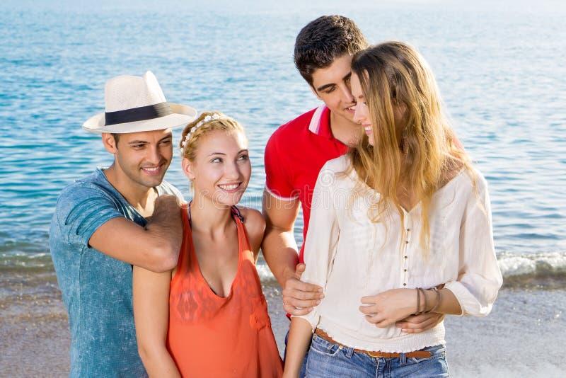 Szczęśliwe potomstwo pary przy plażą fotografia stock