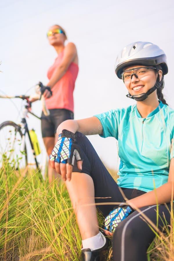 Szczęśliwe pozytywne przyglądające żeńskie sport atlety odpoczywa wpólnie ou zdjęcia stock