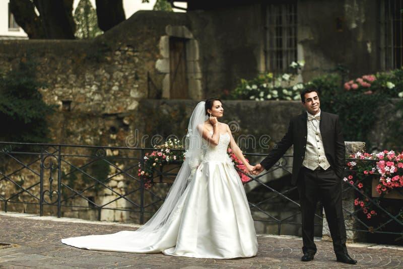 Szczęśliwe romantyczne pary małżeńskiej mienia ręki na kamienia moscie z obrazy stock