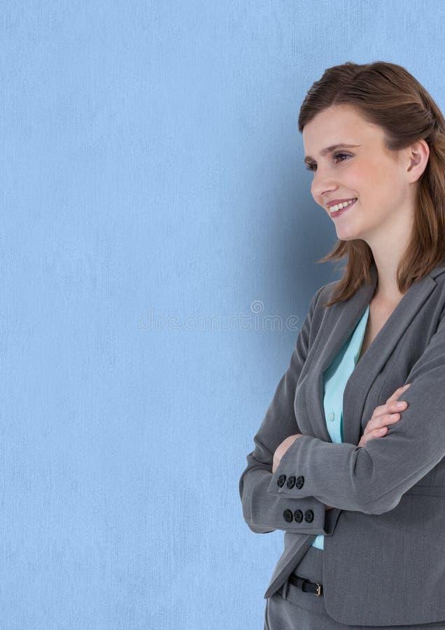 Szczęśliwe rozważne bizneswoman pozyci ręki krzyżowali przeciw błękitnemu tłu fotografia stock
