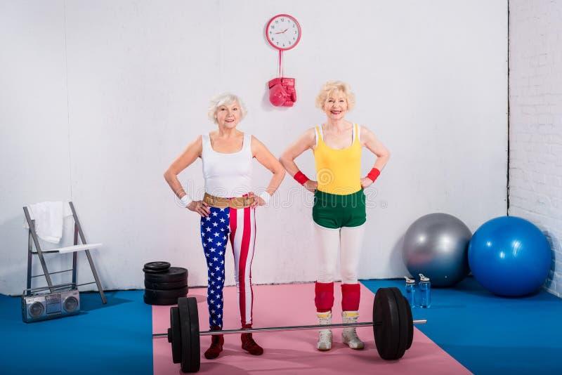 szczęśliwe sporty starsze kobiety stoi z rękami na talii i ono uśmiecha się przy kamerą obrazy royalty free