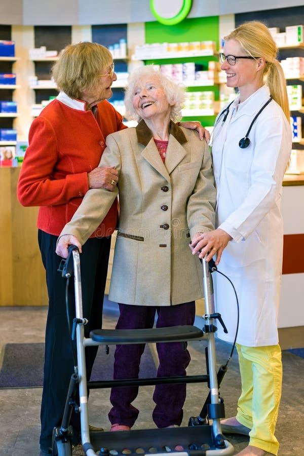 Szczęśliwe starsze kobiety śmia się z lekarką z spacerem obrazy stock
