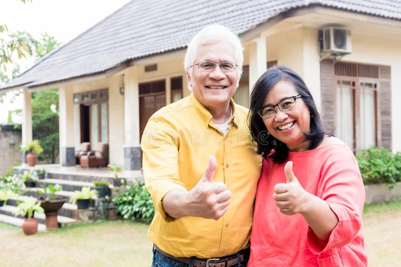 Szczęśliwe starsze osoby dobierają się pokazywać aprobaty przed ich nowym res zdjęcie stock