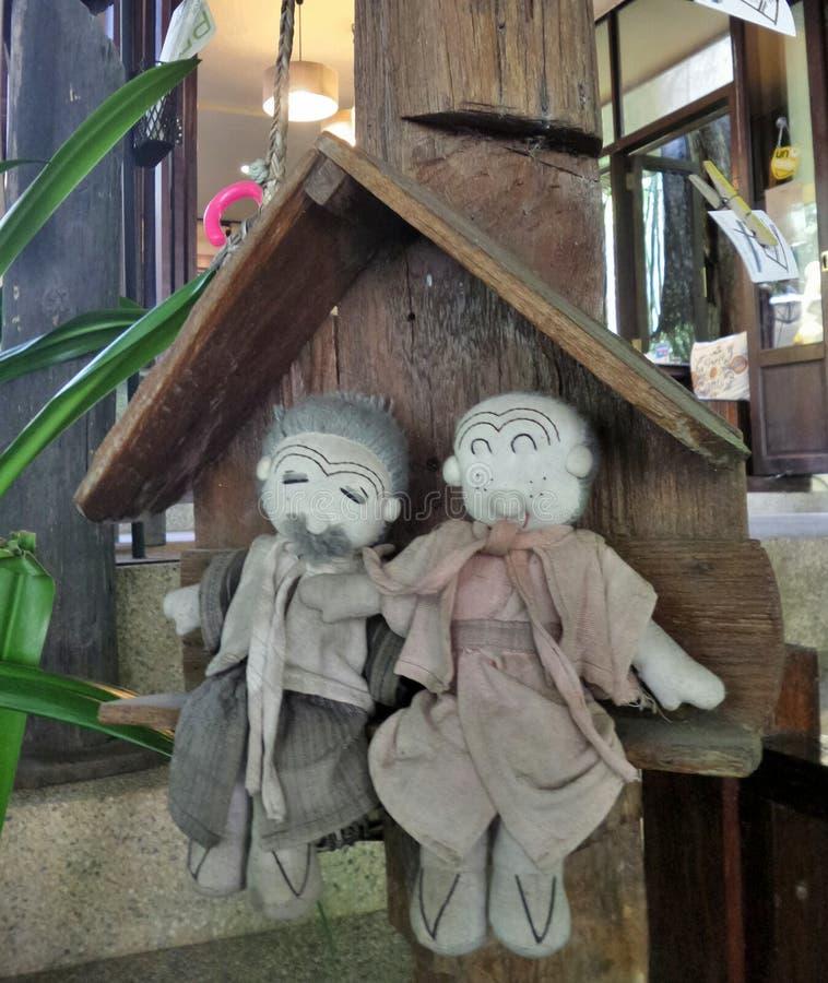 Szczęśliwe starsze osoby siedzi w drewnianej chałupie dobierają się sukienne lale fotografia stock
