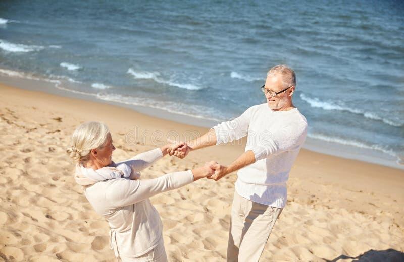 Szczęśliwe starsze pary mienia ręki na lecie wyrzucać na brzeg obrazy stock