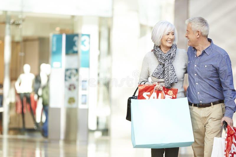Szczęśliwe Starsze pary przewożenia torby W zakupy centrum handlowym zdjęcia royalty free