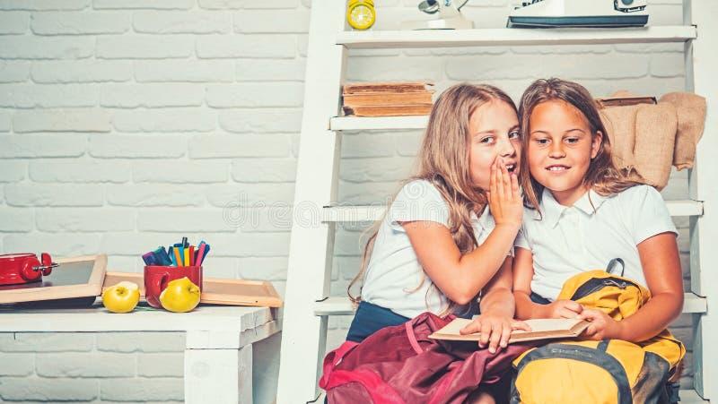 Szcz??liwe szkolne dziewczyny czyta ksi??k? w bibliotece przy szko?? zdjęcia royalty free