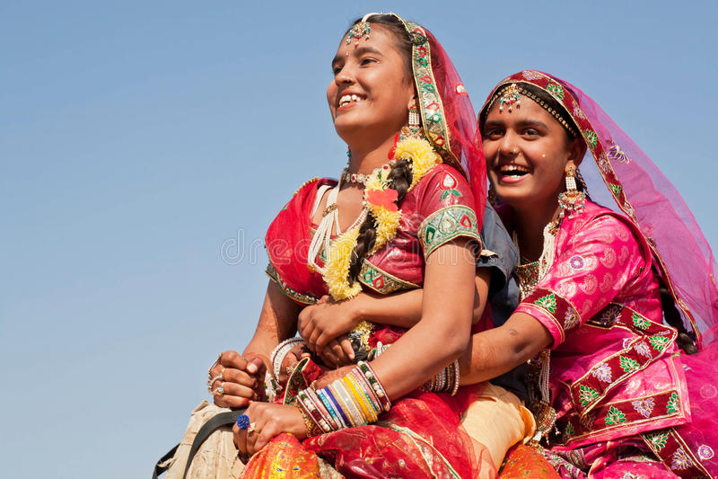 Szczęśliwe twarze wiosek kobiety w czerwonych sukniach jadą wielbłąda zdjęcia stock