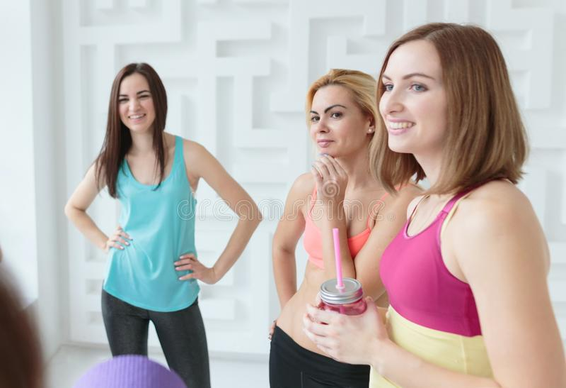 Szczęśliwe uśmiechnięte kobiety gawędzi po ich treningu w sprawności fizycznej studiu obraz stock