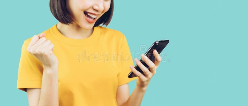 Szczęśliwe uśmiechnięte kobiety i trzymać mądrze telefon z zadziwiający dla sukcesu obraz royalty free