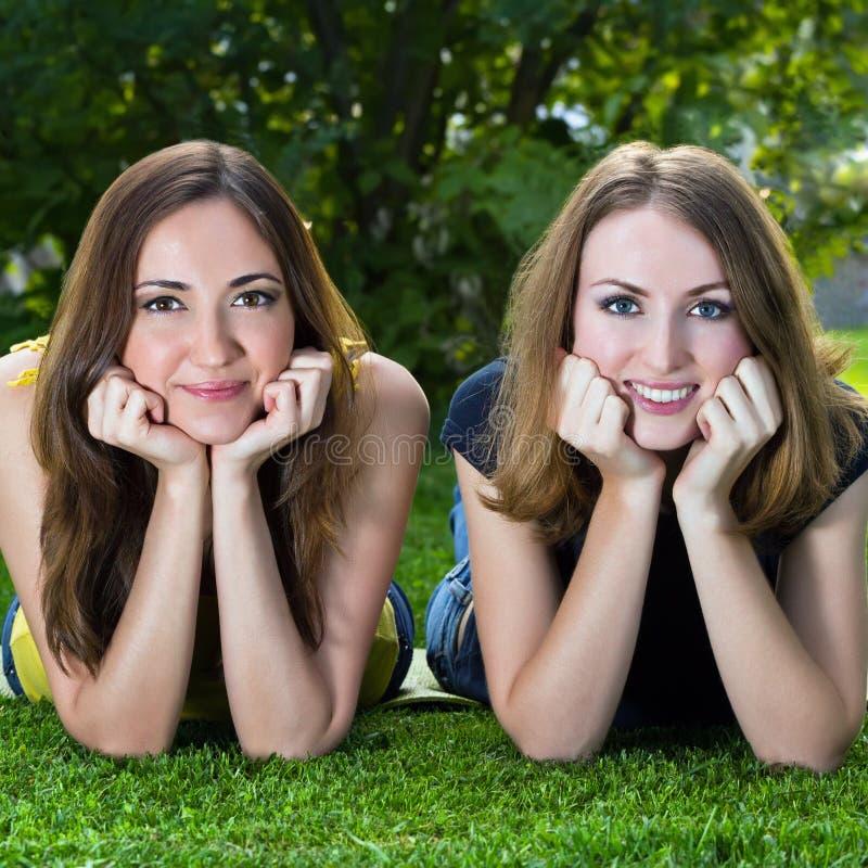 Szczęśliwe uśmiechnięte młode kobiety kłama na trawie obraz stock