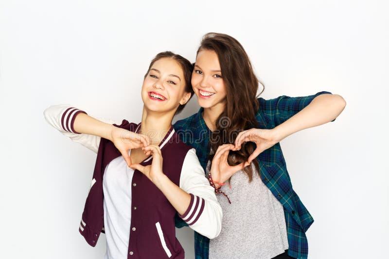 Szczęśliwe uśmiechnięte nastoletnie dziewczyny pokazuje serce śpiewają zdjęcia royalty free