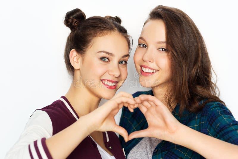 Szczęśliwe uśmiechnięte nastoletnie dziewczyny pokazuje serce śpiewają obrazy royalty free