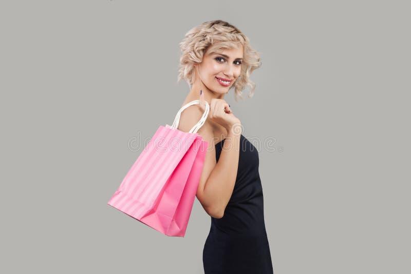 Szczęśliwe wzorcowe mienie menchii torby na zakupy Piękna kobieta z krótkim kędzierzawym włosy i makeup obrazy stock