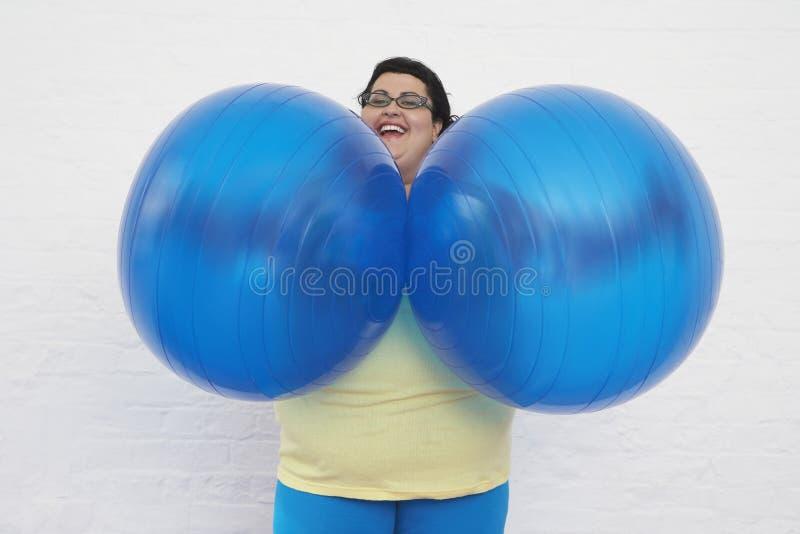 Szczęśliwe Z nadwagą kobiety mienia ćwiczenia piłki zdjęcie stock