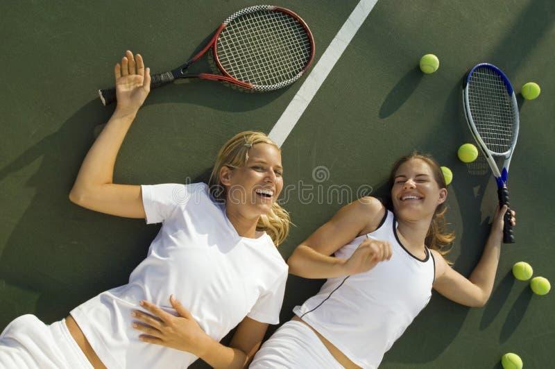 Szczęśliwe Zmęczone kobiety Śmia się Na Tenisowym sądzie fotografia royalty free