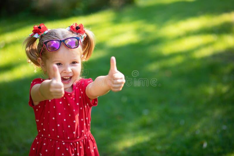 Szczęśliwego śmiesznego blondynki małej dziewczynki przedstawienia celownicze aprobaty i szczęście obraz royalty free