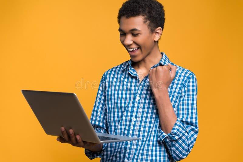 Szczęśliwego Afro Amerykański nastolatek pracuje z laptopem zdjęcia royalty free