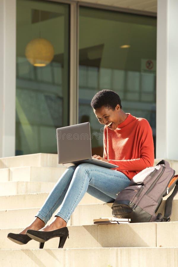 Szczęśliwego amerykanin afrykańskiego pochodzenia żeński uczeń pracuje z laptopem na szkoła wyższa kampusie obraz stock