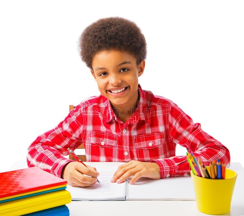 Szczęśliwego amerykanina afrykańskiego pochodzenia szkolna chłopiec bierze test zdjęcia stock