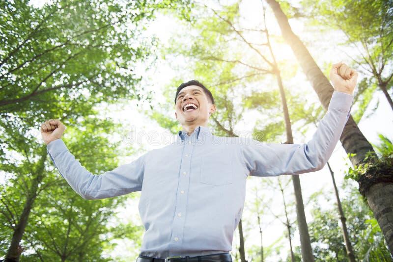 Szczęśliwego azjatykciego biznesmena przesławny sukces plenerowy zdjęcia stock