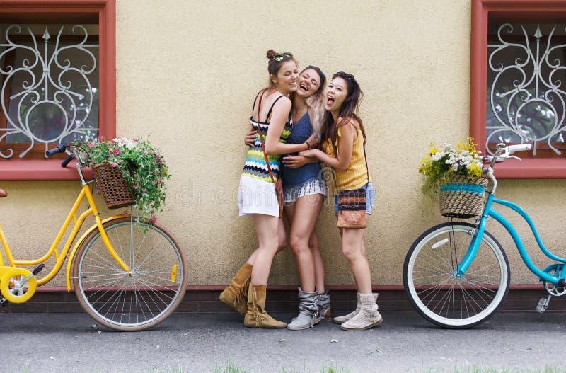 Szczęśliwego boho dziewczyn modna poza z bicykl pobliską domową fasadą zdjęcie royalty free