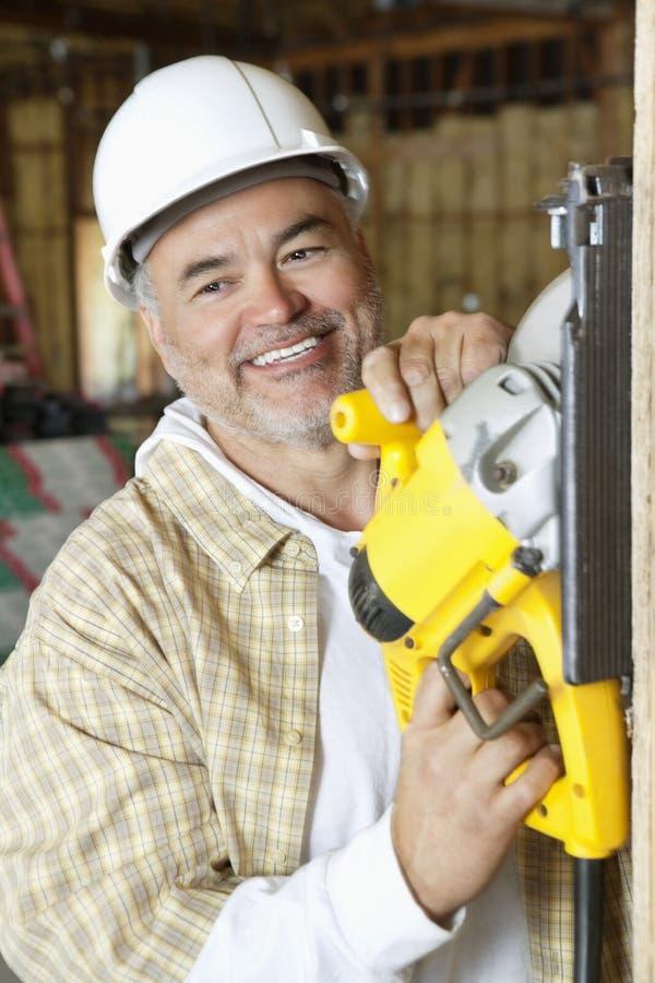 Szczęśliwego dojrzałego męskiego pracownika budowlanego tnący drewno z kółkowym saw zdjęcia stock