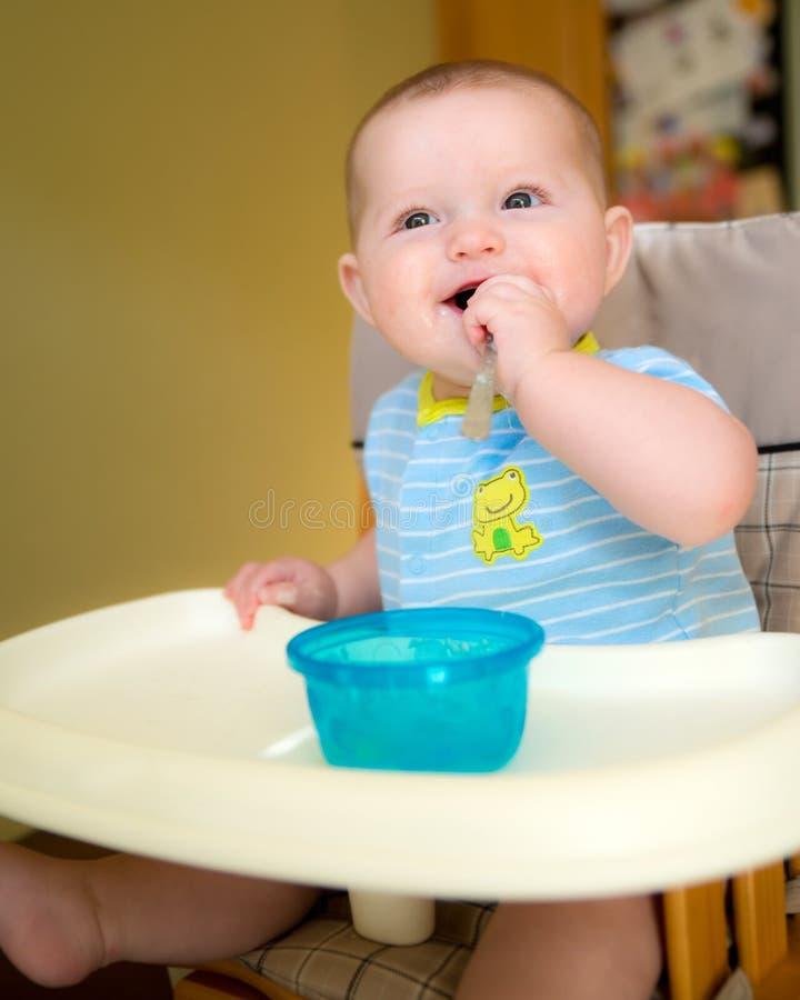 Szczęśliwego dziecka chłopiec łasowania dziecięcy posiłek fotografia royalty free