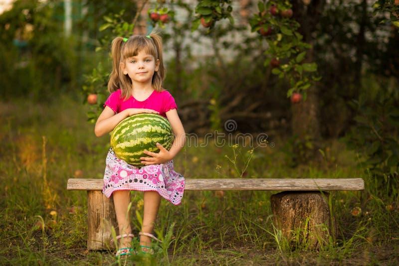 Szczęśliwego dziecko dziewczyny chwyta prawdziwy duży arbuz w słonecznym dniu pojęcie zdrowy zdjęcie royalty free