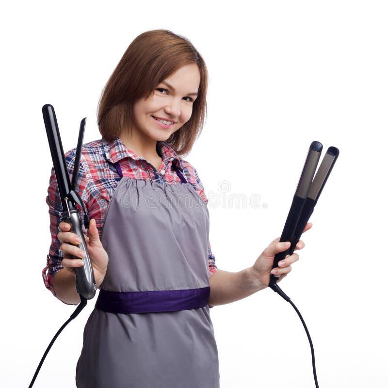 Szczęśliwego fryzjera mienia włosiana prostownica na białym backgropund zdjęcie stock
