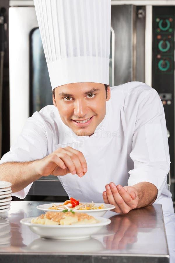 Szczęśliwego Męskiego szefa kuchni Tryskaczowe pikantność Na naczyniu zdjęcia royalty free