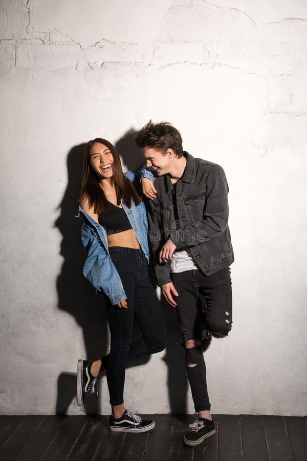 Szczęśliwego młodego modnisia kochająca para patrzeje na boku obraz stock