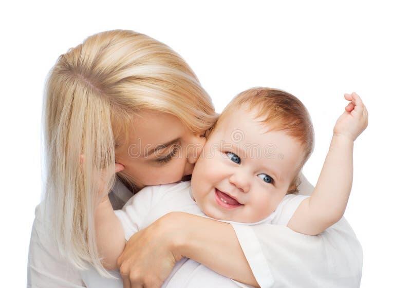Szczęśliwego macierzystego całowania uśmiechnięty dziecko obraz royalty free