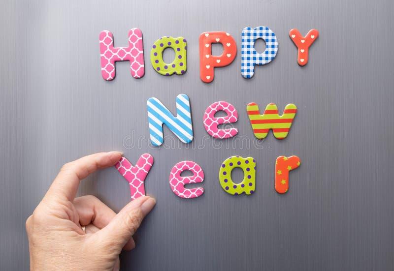 Szczęśliwego nowego roku, dłoni, robiąc wiadomość z liter magnetycznych na lodówce zdjęcia royalty free