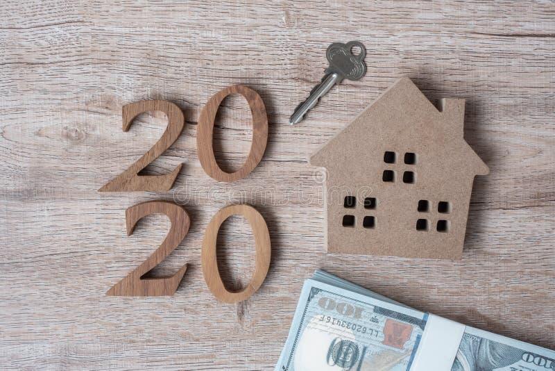 Szczęśliwego Nowego Roku 2020 z modelem domu i pieniędzmi na drewnianym tle Bankowość, nieruchomości, inwestycje, finanse, oszczę obrazy stock