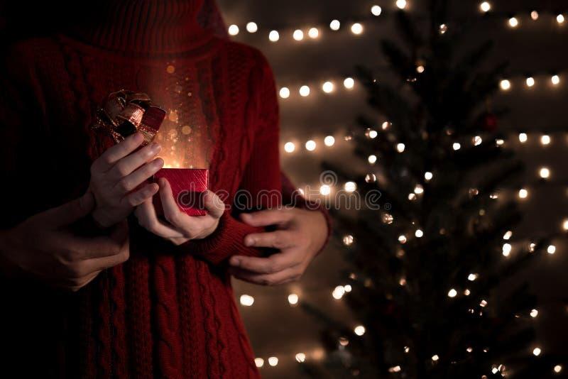 Szczęśliwego pary otwarcia Bożenarodzeniowi prezenty z złocistymi magicznymi światłami obraz stock