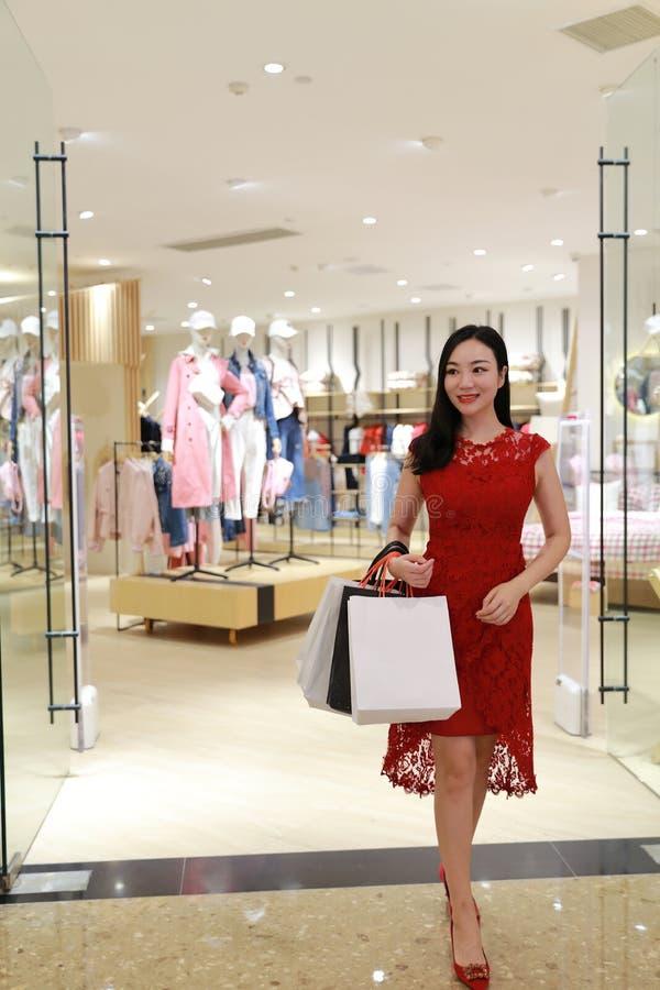 Szczęśliwego piękna modnej kobiety dziewczyny zakupy Azjatycka Chińska nowożytna karta i torba na ręce w centrum handlowym przech obraz stock