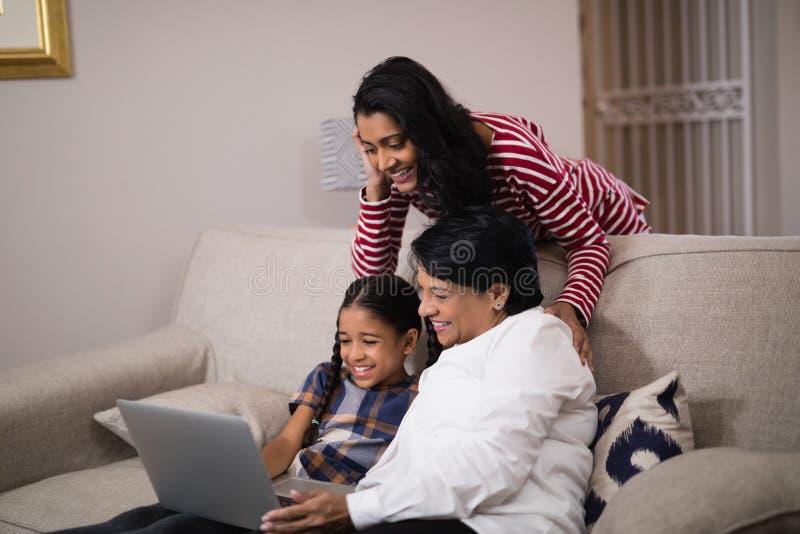Szczęśliwego pokolenia rodzinny używa laptop wpólnie fotografia royalty free