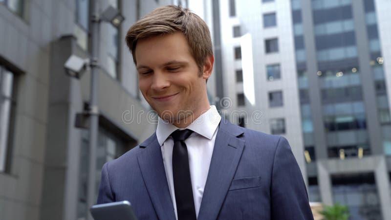 Szczęśliwego pracownika czytelniczy email na telefonie, dobre wieści o promocji, rozpoczęcie obrazy stock