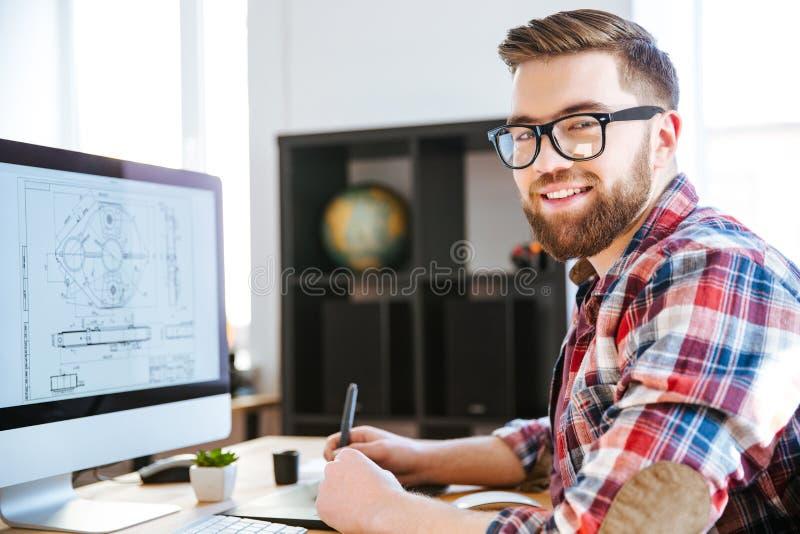 Szczęśliwego projektanta rysunkowy projekt na komputerowej używa pióro pastylce fotografia royalty free