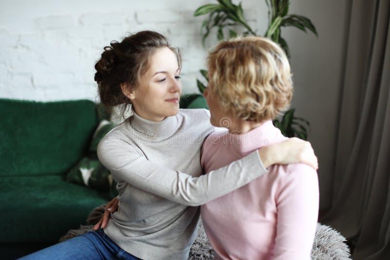 Szczęśliwego senior matki obejmowania dorosła córka śmia się wpólnie, uśmiechnięta z podnieceniem starzejąca się starej damy przy zdjęcia stock